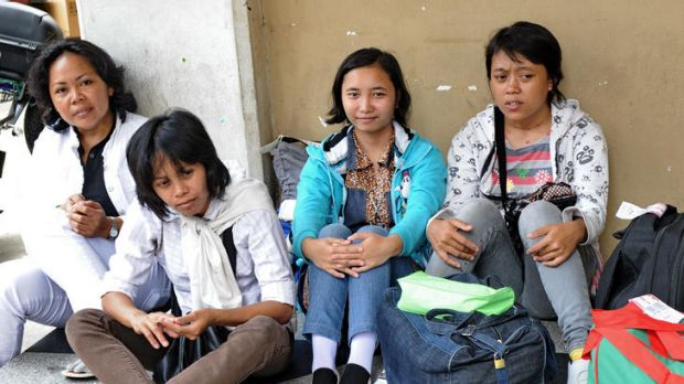 Newly arrived domestic helpers from Indonesia wait for their transportation to a maid agency after going through medical ...