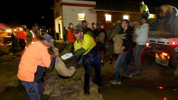 Residents, emergency crews and members of the army rush to sandbag Weir Street