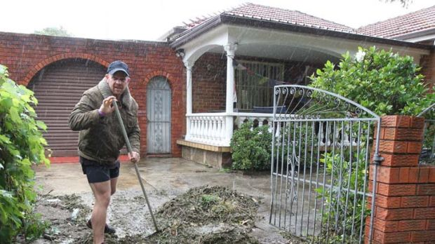 The big clean up ... Resident James Buckle of Marrickville rolls up his sleeves after floodwaters recede.