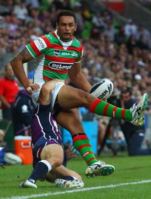 John Sutton of the Rabbitohs is tackled by Cooper Cronk.