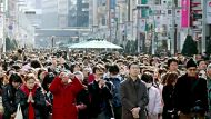 Pedestrians offer prayers at 2:46 p.m., the moment the magnitude-9.0 quake struck a year ago, for the disasters' ...
