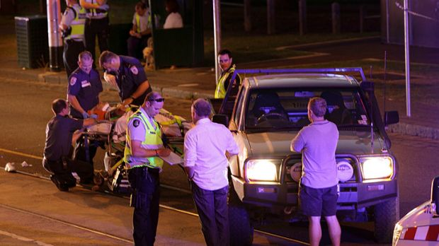 An injured pedestrian is stretchered from the scene of a fatal crash on Toorak Road at South Yarra this morning.