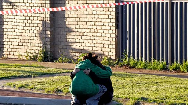 Grief ... Emotions are run high outside the burned house in Melton South, where a man has lost his life.