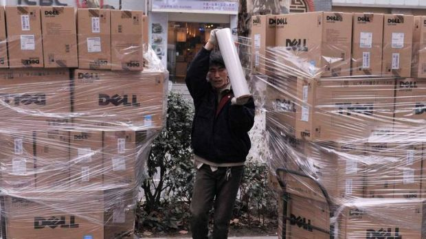 A worker uses a roll of plastic tape to secure Dell boxes at a street near an electronic products market in Nanjing, ...