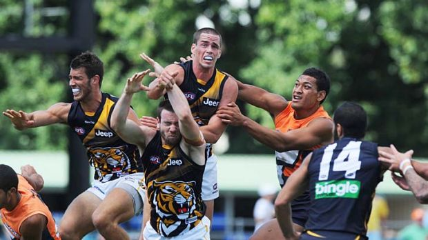 Giant challenge: Greater Western Sydney's Israel Folau (second from right) tries to tackle a Richmond opponent yesterday ...