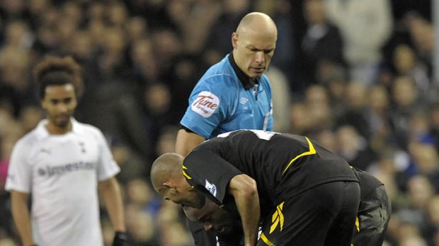 Referee Howard Webb look on as Bolton's English midfielder Fabrice Muamba is treated by medical staff.