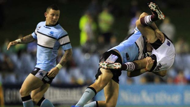 Shark pounces … Cronulla's John Williams tackles Manly's Michael Oldfield at Toyota Park last night, closely ...
