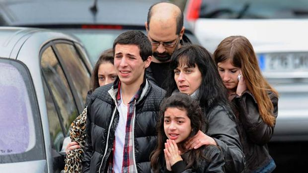 Deadly attack ... children and adults look on after the shooting at the Ozar Hatorah school.