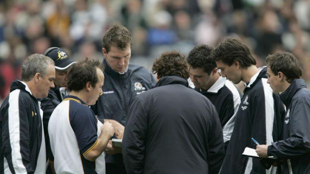 Jim Stynes, centre, speaks with Australian coach Gary Lyon (third from right) and the rest of the team's coaching staff ...