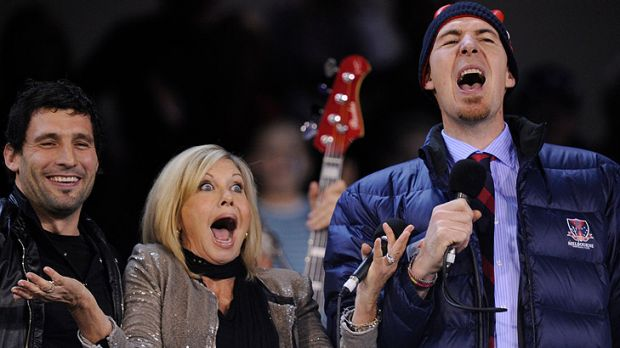 Playful ... Jim Stynes sings along with Olivia Newton John and  Russell Robertson before a Melbourne vs Carlton game in ...