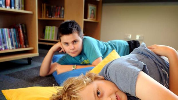 Two of Clifton Hill Primary School's autistic students, Mitchell Swannie (back) and Adam Dickson in the school library.