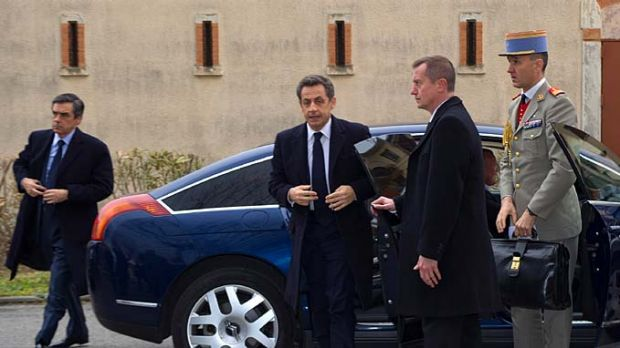 French President Nicolas Sarkozy arrives in Toulouse as police and response teams surround a property nearby.