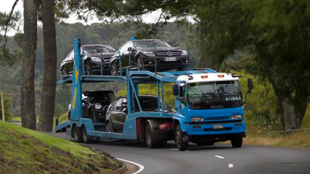 Police remove vehicles belonging to Kim Dotcom from his home during the January raid.