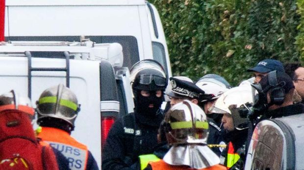 Police and members of the emergency services surround the property during an operation to arrest suspected gunman ...