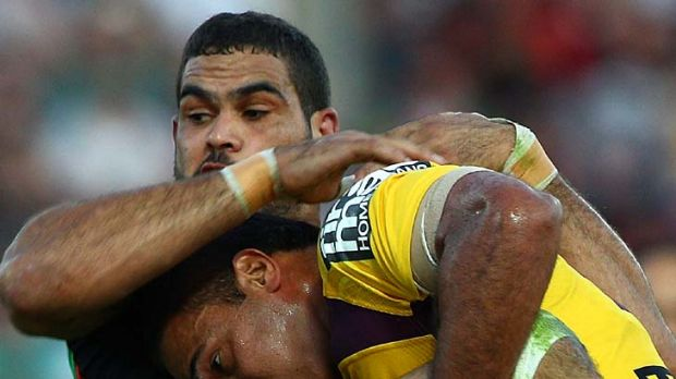 Greg Inglis of the Rabbitohs is tackled by Justin Hodges.