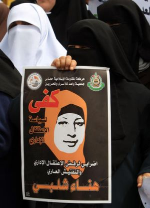 A Palestinian woman holds a banner reading 'Enough to administrative detention' during a rally in Gaza City.