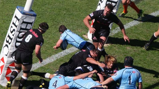 Diving in … halfback Brendan McKibbin plunges between two defenders and under the posts to score for the Waratahs ...
