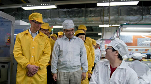 This handout picture released by Apple and taken on March 28, 2012 shows Apple chief executive Tim Cook (L) visiting the ...