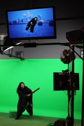 A girl rides a broomstick in front of a green screen. March 23, 2012.
