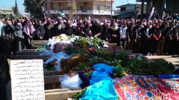 Syrians attend a mass funeral for people whom anti-government protesters said were killed by the shelling in Al Qasseer ...