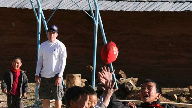 Lifting spirits: Swans' Jared Crouch watches Chinese children play with a football he and teammate Ryan O'Keefe gave them.