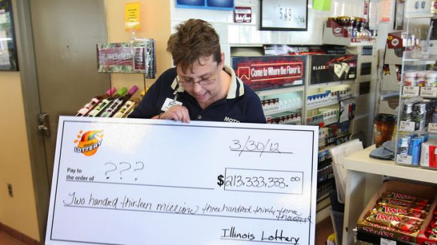 Illinois Moto Mart store manager Denise Metzger looks at an oversized cheque given to her by lottery officials