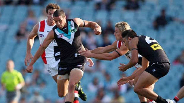 Tough contest: Port's Travis Boak goes hard at the ball at AAMI Stadium yesterday.