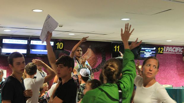 Passengers at Nadi International Airport in Fiji scramble for flights out of the country.