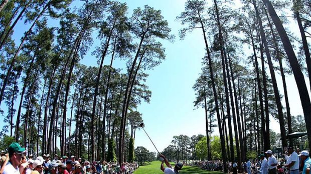 Adam Scott hits a tee shot in front of a gallery of patrons during a practice round at Augusta.