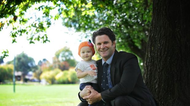 Chris Cairns with his daughter Isabel. Isabel has just received a cochlear implant and can now hear for the first time.