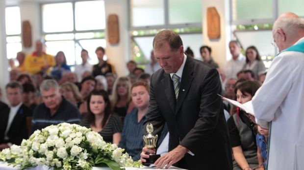 Steve Barclay places a trophy on top of his son Matt Barclay's coffin.