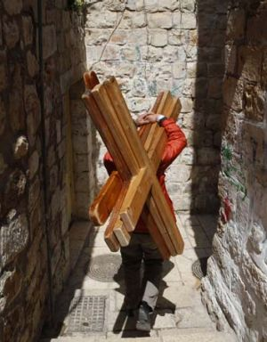 In demand ... Mazen Khanan, a Muslim who hires crosses to visiting Christians, carries four to the First Station of the ...