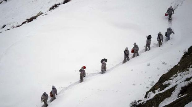 Pakistani soldiers carry supplies up the mountain near their outpost in Pakistan's Dir district.