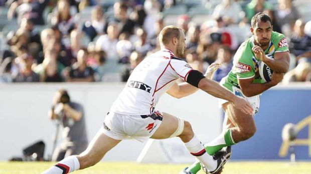 Reece Robinson of the Raiders is tackled by Simon Mannering of the Warriors.