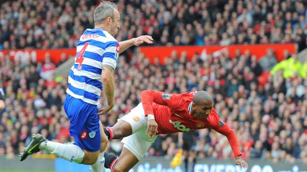 Uproar: United's Ashley Young was supposedly fouled by QPR's Shaun Derry (left) in this incident, which ended in a ...