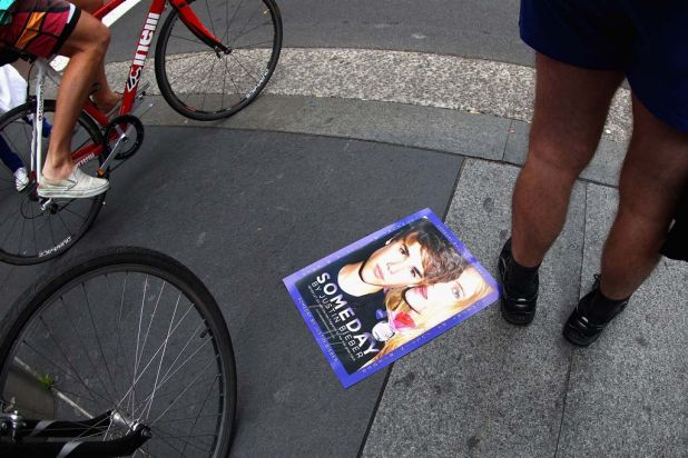 Forgotten ... a Justin Bieber poster lies discarded as fans gather in Martin Place for a glimpse of One Direction.