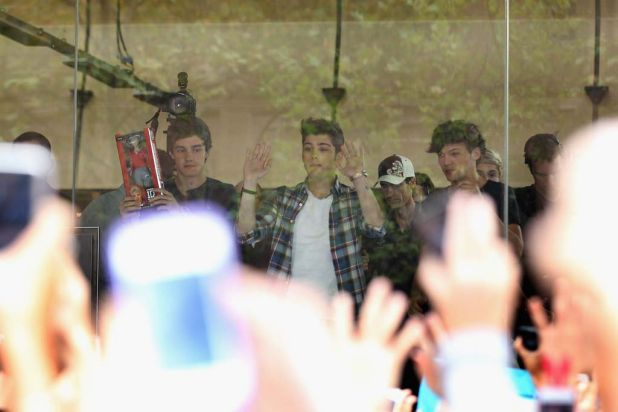 As close as they got ... boy band One Direction gesture to thousands of fans gathered in Martin Place.