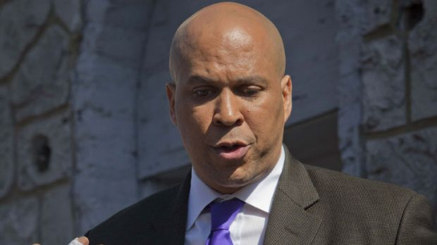 Newark mayor Cory Booker speaks to the media outside the house from which he saved a neighbour.