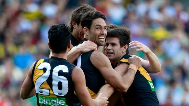 Ex-Demon Brad Miller is congratulated by teammates after kicking a goal.