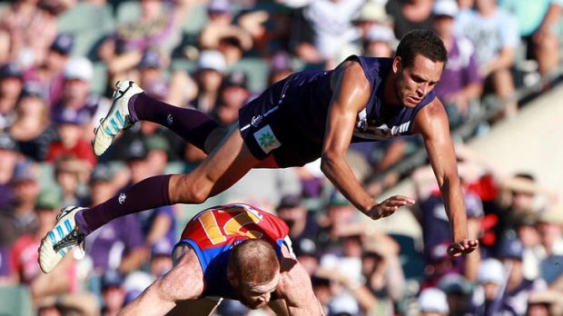 The Dockers Michael Johnson is up-ended by Daniel Merrett of the Lions yesterday.