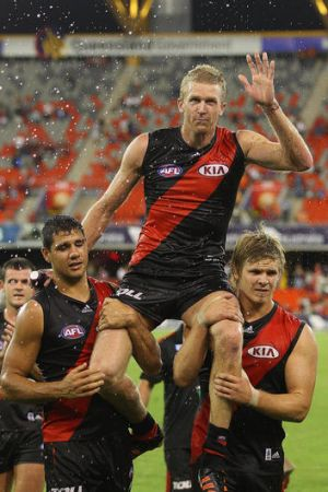 Dustin Fletcher of the Bombers is carried from the field after his 350th game.