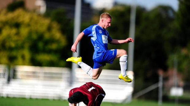 Tuggeranong United goalkeeper Matt MacDonald takes evasive action from Canberra Olympic's Oliver Weiderkehr.