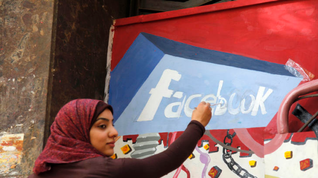 An Egyptian student paints the Facebook logo on a mural commemorating the revolution that overthrew Hosni Mubarak. ...