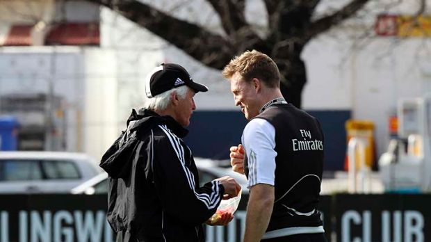 Magpies coach Mick Malthouse (left) shares a lolly from his lolly bag with assistant coach Nathan Buckley during a ...
