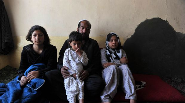 Tarana Akbari, right, sits in her Kabul home with her father, sister and brother.