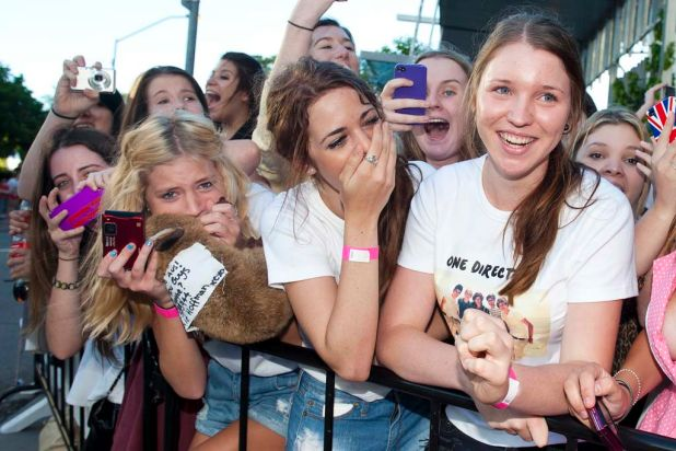 Excited fans watch as One Direction arrive for their concert at the Brisbane Convention and Exhibition Centre.