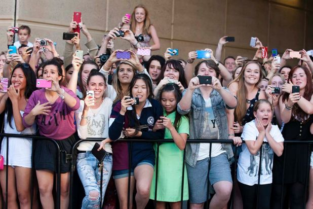 Fans take pictures as One Direction arrive for their concert at the Brisbane Convention and Exhibition Centre.