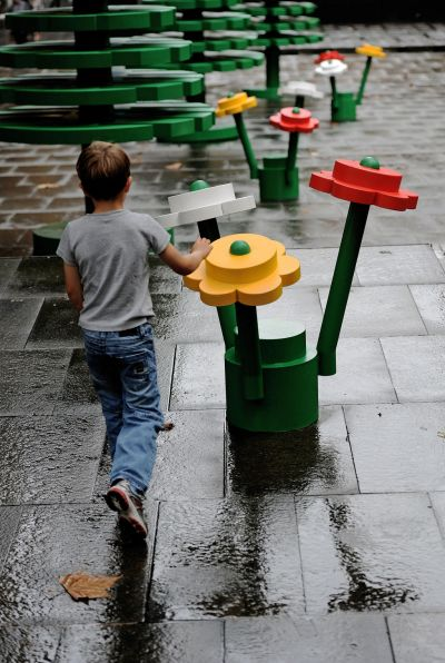 A young boy walks through a life-sized LEGO forest during a wet morning in Sydney. AFP PHOTO / Greg WOOD