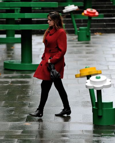 A woman walks through a life-sized LEGO forest during a wet morning in Sydney. AFP PHOTO / Greg WOOD