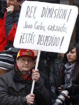 "A protestor holds a banner reading ""King, abdication! Juan Carlos, caught. You are fired!"" outside the exit of a ..."
